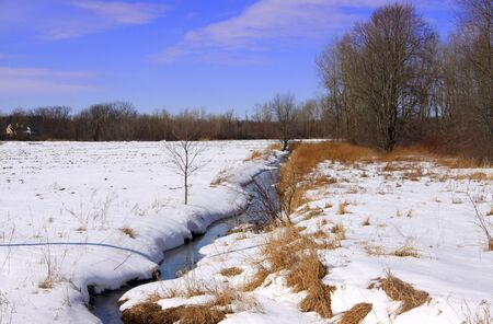 Stream flowing through snow covered fields in winter time photo