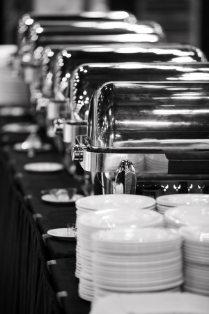 Many buffet trays ready for service in black and white.