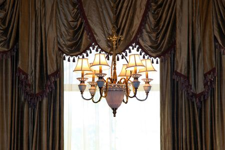 Chandelier and curtains of a luxury home window photo