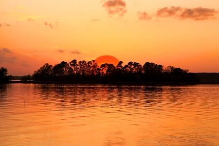 Bright orange sky with Sun set over island  Standard-Bild