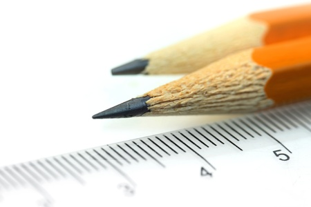pencil symbol: Close up shot of two sharpened pencil and scale Stock Photo