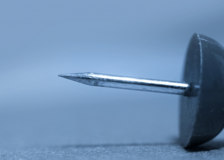 push: Close up shot of push pin in blue color tone