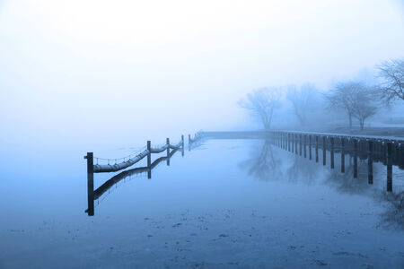Mist over the lake on winter morning photo