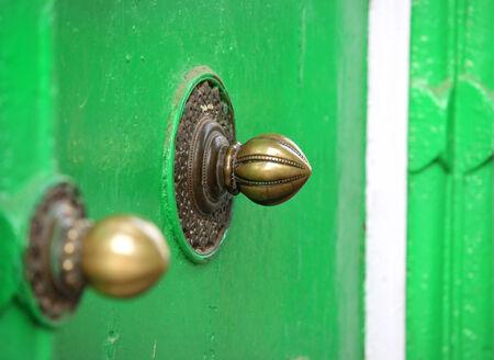 Two old door knobs on the green door photo