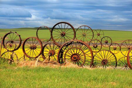america countryside: Rusty wheels fence Stock Photo