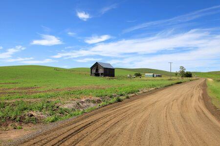 unpaved road: Gravel road through farms