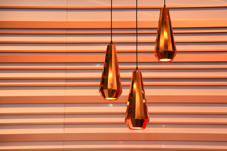 luminaire: Three modern  lamps against striped wall