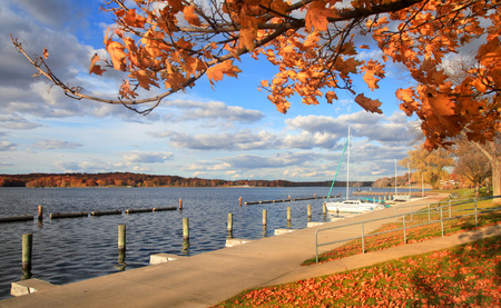 docked: Boats docked in a lake by the autumn trees Stock Photo