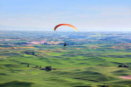 Para glider up in sky above rolling hills Stock Photo