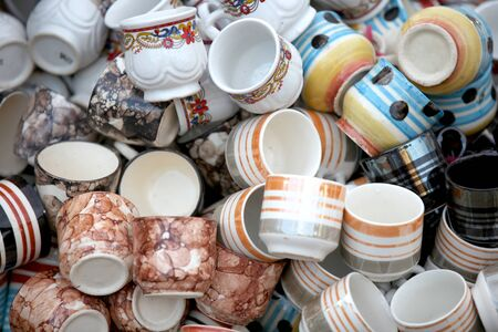 Many clay cups randomly arranged for sale