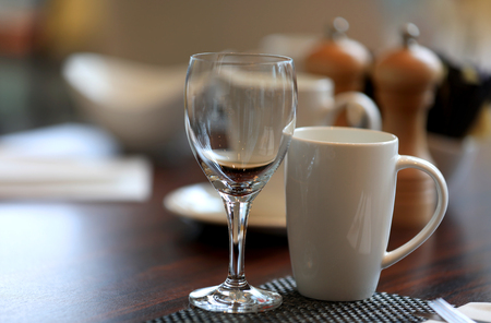 Wine glass and coffee cup on breakfast table