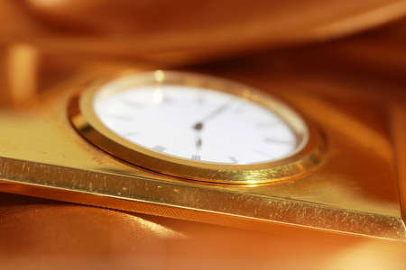 Old golden clock wrapped in a golden satin cloth