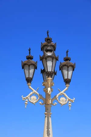Traditional decorative lamp post against blue sky background