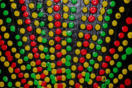 Abstract background of colorful painted dot on black paint