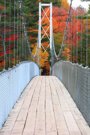 Tall suspension bridge with fall foliage in rural Quebec 版權商用圖片