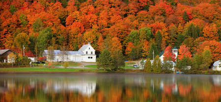 Panoramic view of old barn by the lake with fall foliage near Danville, Vermont