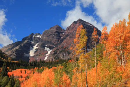 Colorful autumn trees in front of Iconic Maroon bells in Colorado