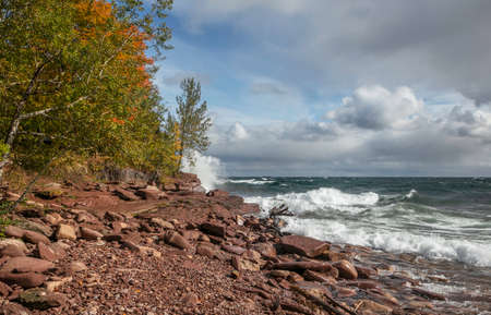Autumn trees along scenic Superior lake shore with waves hitting rocks. 版權商用圖片