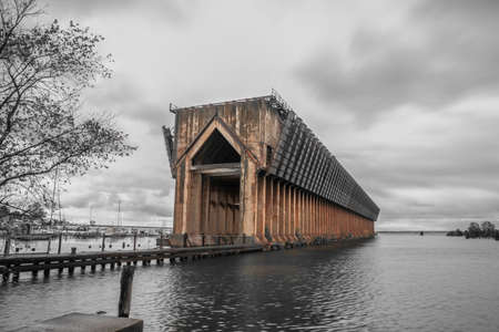 Abandoned old ore dock in lake Superior near Marquette city, in the past this large structure is used to transfer iron coal ore from rail road to ships. Monochrome shot with only ore dock in color.
