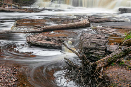 Running water over rocks  at Manido falls with dead trees in the water in rural Michigan upper peninsula Standard-Bild
