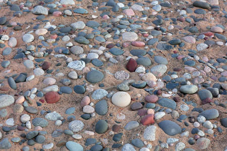 Colorful stones embedded in the sand bed along lake Superior shore line