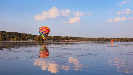 Hot air balloon flying over close to Kent lake in Michigan, USA