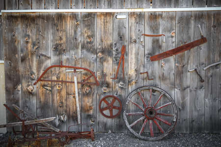 Old rusty tools in on abandoned barn wall.