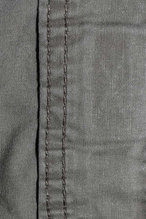 Close up shot of grey fabric with stitches