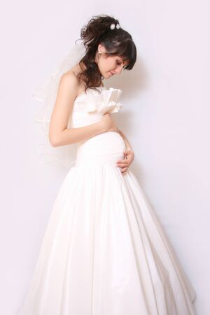 A pregnant bride on a white background photo