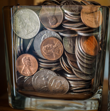 miser: Savings Jar Full Of Money and US Coins Stock Photo
