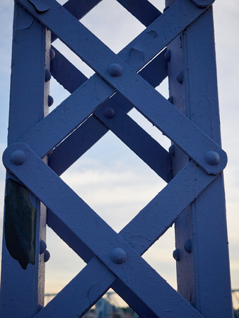 dutch: Detail shot of an historic gray painted Dutch riveted truss bridge against a blue sky. Stock Photo