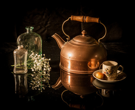 Still life with antique brass tea pot, coffee cup, flower, bottle Stock Photo