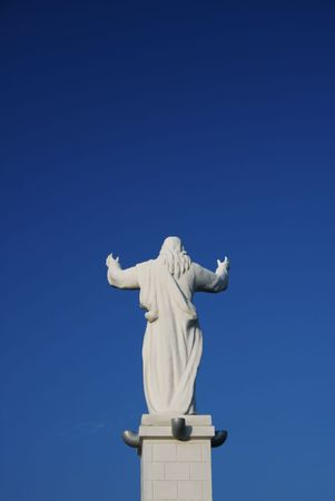 Jesus's statue from the back on a blue sky Stock Photo - 591268