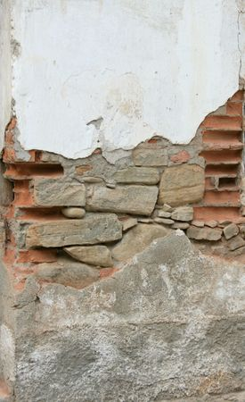 disrupted: 3 texture in a single wall: a disrupted wall with stucco, broken bricks, stone and concrete