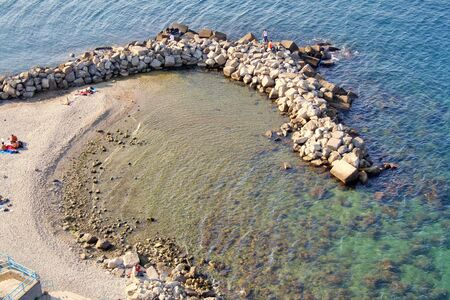 mediterrean: A beach in mediterrean sea protected by a tongue of pilled rocks