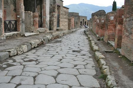 An antique roman stone street through ruins of Pompei,Italy. Stock Photo