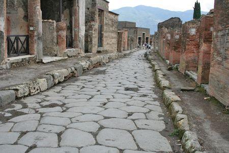 An antique roman stone street through ruins of Pompei,Italy. Stock Photo