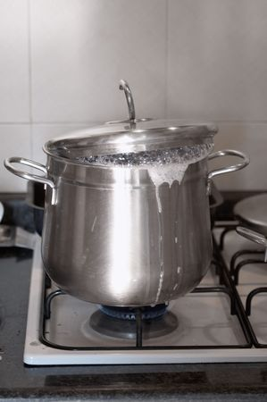 A boiling pot on a gas burner. Foam flowing out. Stock Photo