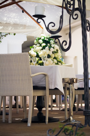 An elegant outdoors table setting with chairs at a luxury hotel in Capri surrounded by flowers, partially behind an iron candelabrum and below a parasol Stock Photo