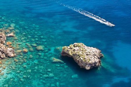 Rocky coastline in Capri.  Sea surface with rocks and a boat.