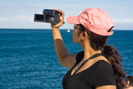 Teenager tourist filming her beach vacation with a compact video camera. photo