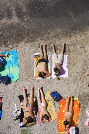 high angle view: A crowded beach in Sorrento,Italy. Boys and girls sunbathing. Top view.