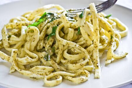 pesto: Scialatielli (spaghetti-like pasta) with pesto sauce.A typical italian dish. Picking up with a fork.