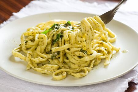 Scialatielli (spaghetti-like pasta) with pesto sauce.A typical italian dish. Picking up with a fork.