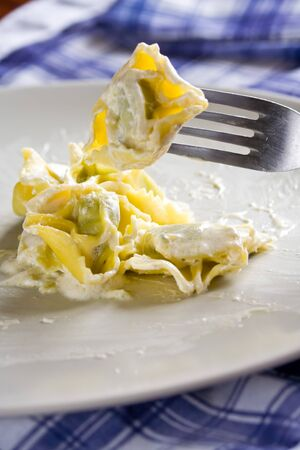 Tortellini pasta with cream sauce, an italian dish. Picking with a fork. Stock Photo