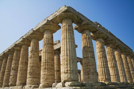 The temple of Hera, built around 550 BCE by Greek colonists, in Paestum, Italy. Low angle view against blue sky