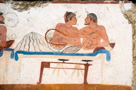 Ancient Grrek Fresco in Paestum, Italy, depicting a couple of men during a banquet
