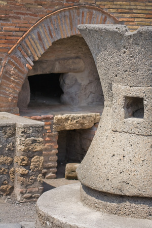 Ancient Bakery in Pompeii, Italy. Detail of grindstone and oven in the background Stock Photo