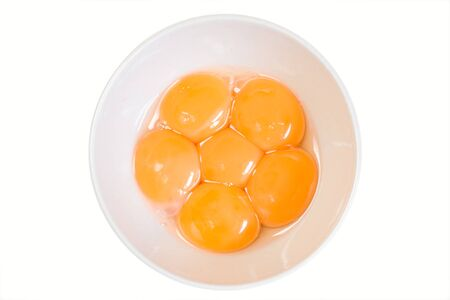 Raw egg yolks in a bowl as used in cooking. Isolated on white.