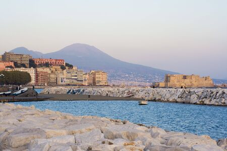 View the gulf of Naples at dusk. City coastline panorama with Mt.Vesuvius on the back and Castel dellOvo (Egg Castle), in the bay. Italy.